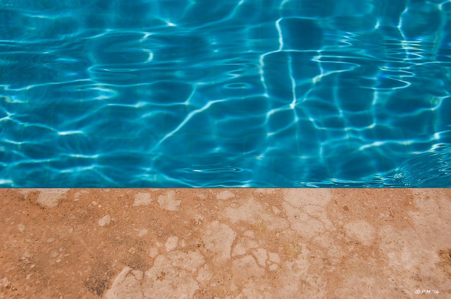 Swimming pool with bright blue water and orange stone edge at base of frame. Abstract Colour. Patara, Turkey. P.Maton 2014