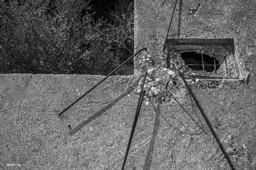 Bent rebar and square hole in concrete roof with olive trees below, monochrome abstract. Patara, Turkey. P.Maton 04/09/2014 eyeteeth.net