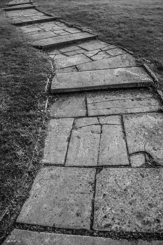 Old flagstone path with steps snakes away from the camera through mown grass, St Nicholas Church Green Space, Brighton, East Sussex UK.. Monochrome abstract.  P.Maton 2014 eyeteeth.net