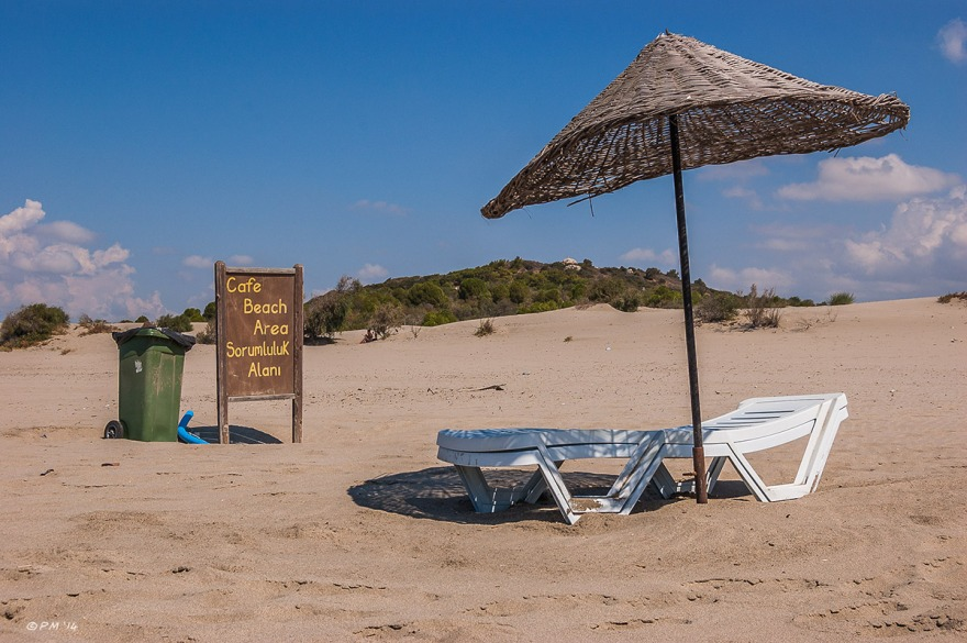 Woven parasol over sun lounger next to rubbish bin and sign on Gelemis Beach, Turkey. Colour landscape. P.Maton 2014 eyeteeth.net