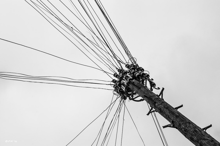 Telegraph pole with radiating telephone cables silhouette against grey overcast sky . Monochrome landscape abstract. © P.Maton 2014 eyeteeth.net