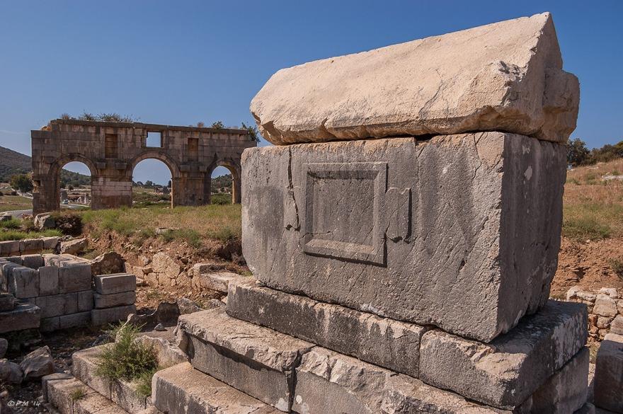 Tepecik Necropolis sarcophagus with Triumphal Arch of the Mettius Modestus in background, Gelemiş, Patara, Turkey. Colour landscape. P.Maton 05/09/2014 eyeteeth.net