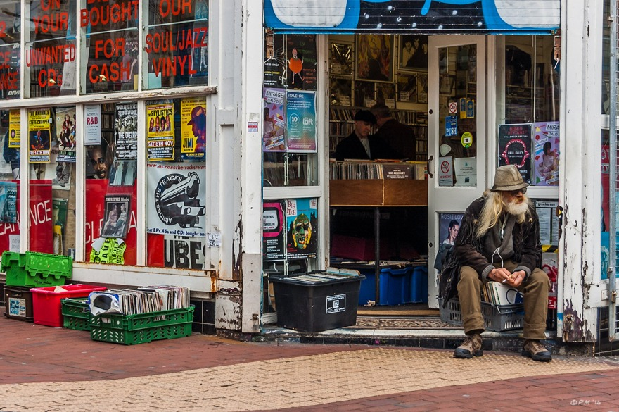 Old man siting on box of records smoking a cigarette in doorway of Across The Tracks record store Sydney Street Brighton UK. Colour landscape. © P.Maton 2014 eyeteeth.net