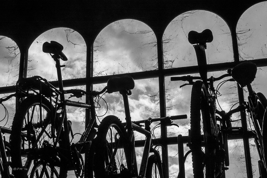Bicycle rack at Brighton railway station silhouetted against arched windows with clouds in background. Monochrome landscape. © P.Maton 2014 eyeteeth.net