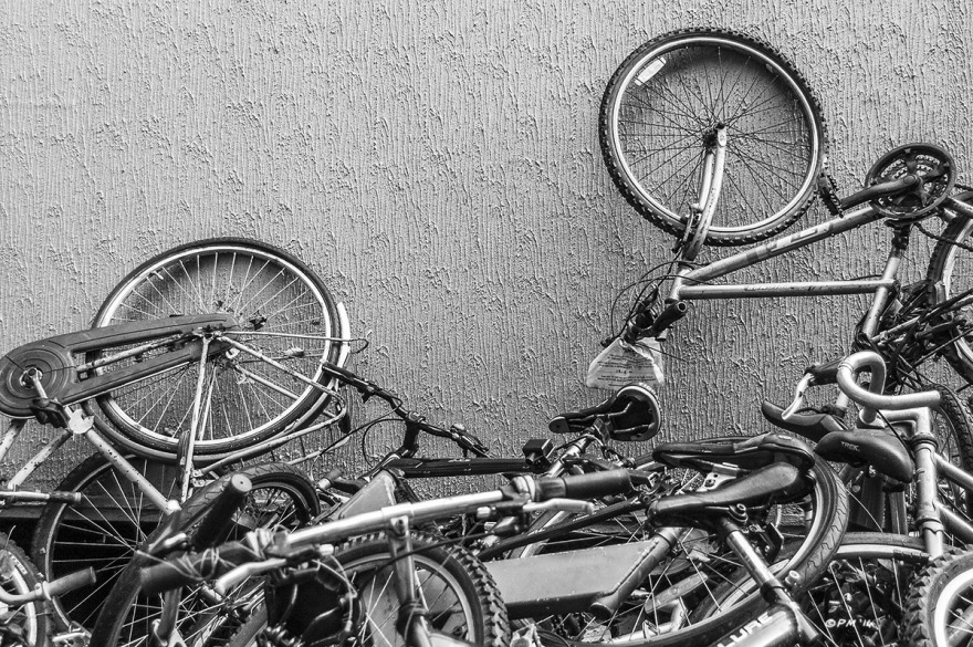 Broken bicycles piled against wall awaiting refurbishment. Monochrome landscape. © P. Maton 2014 eyeteeth.net