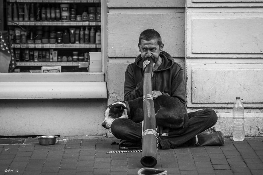 Man playing didgeridoo sitting on pavement with dog on lap. Monochrome landscape. Gardener Street, Brighton, UK © P.Maton 2014 eyeteeth.net