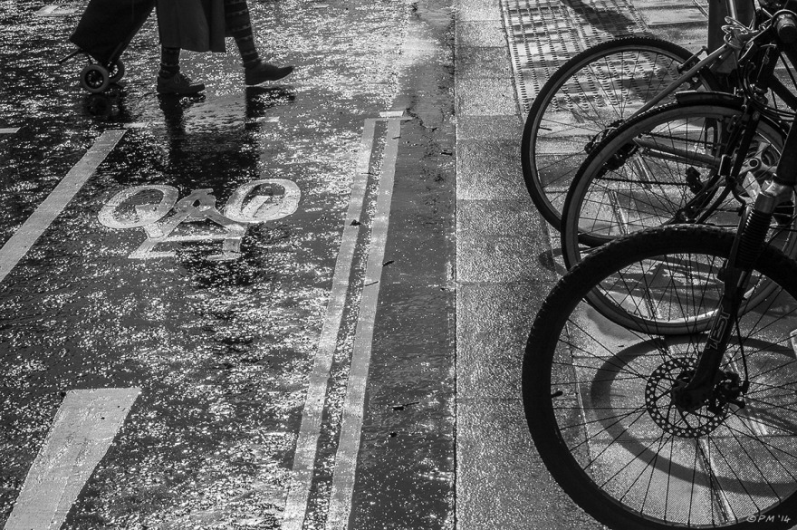 Cycle rack, curb stones and lady with trolley crossing wet road  monochrome abstract landscape. © P.Maton 2014 eyeteeth.net