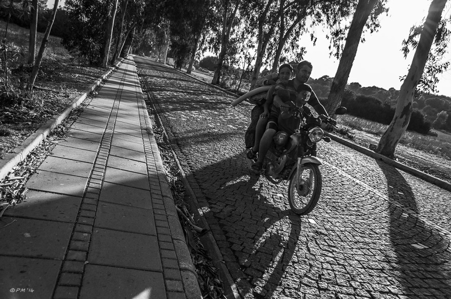 Family riding on motorbike along cobbled road from Gelemis beach to Patara with sun behind and long shadows. Monochrome Landscape. Turkey. © P.Maton 2014 eyeteeth.net