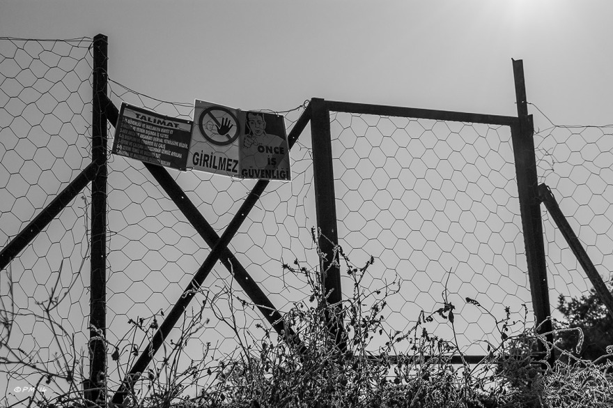Fence with warning signs around archaeological dig of the Dynast Residence Patara Turkey. Monochrome landscape abstract.  © P.Maton 2014 eyeteeth.net