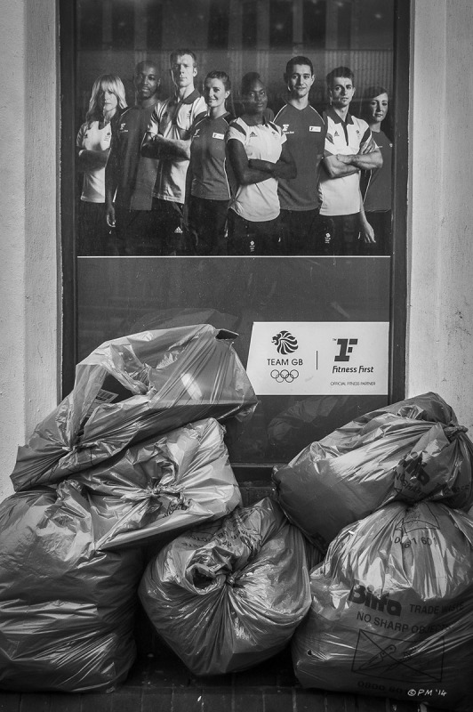 Refuse sacks piled in front of window of Fitness First Gym, Queen Street Brighton. Monochrome Portrait. © P.Maton 2014 eyeteeth.net