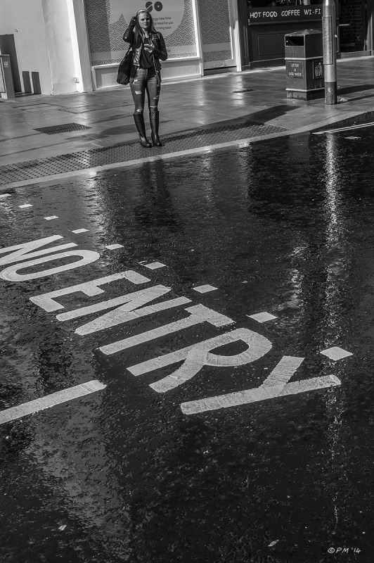 Girl with phone standing at road crossing on far side of wet road.monochrome portrait. © P.Maton 2014 eyeteeth.net