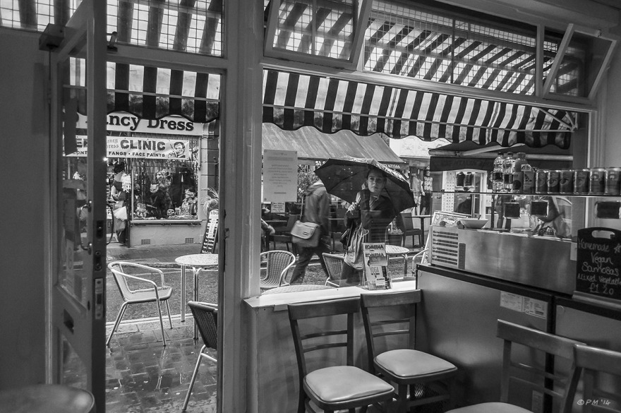 View from inside We Love Falafel shop on to Sydney Street with Girl holding umbrella looking though window. Brighton UK. Monochrome landscape. ©2014 P.Maton eyeteeth.net