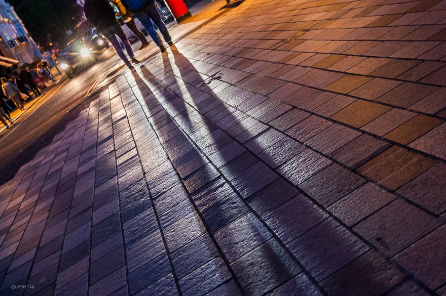 Long shadows cast across pavement by two people walking in front of car headlamps on New Road junction with Church Street Brighton UK. Colour Landscape abstract. © P.Maton 2014 eyeteeth.net