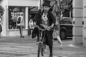 Oriental lady in top hat and black coat and skirt riding small bicycle. Monochrome landscape. Gardener Street, Brighton, UK © P.Maton 2014 eyeteeth.net