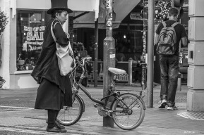 Oriental lady in top hat and black coat and skirt standing next to small bicycle. Monochrome landscape. Gardener Street, Brighton, UK © P.Maton 2014 eyeteeth.net