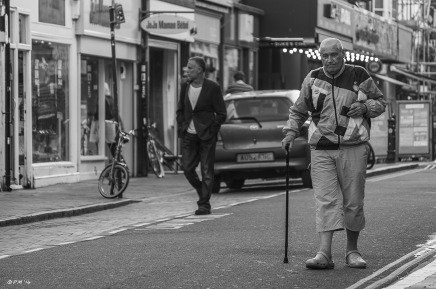 Man with walking stick wearing Crocks walking down street towards viewer. Oriental lady in top hat and black coat and skirt riding small bicycle. Monochrome landscape. Gardener Street, Brighton, UK © P.Maton 2014 eyeteeth.net