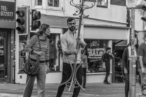 Man in street caring wooden hat stand coat stand. Monochrome landscape. Gardener Street, Brighton, UK © P.Maton 2014 eyeteeth.net