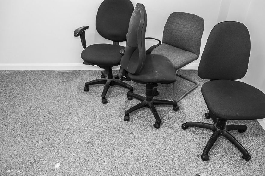 Office chairs in corner of room with dirty carpet. Monochrome landscape.  P. Maton  2014 eyeteeth.net