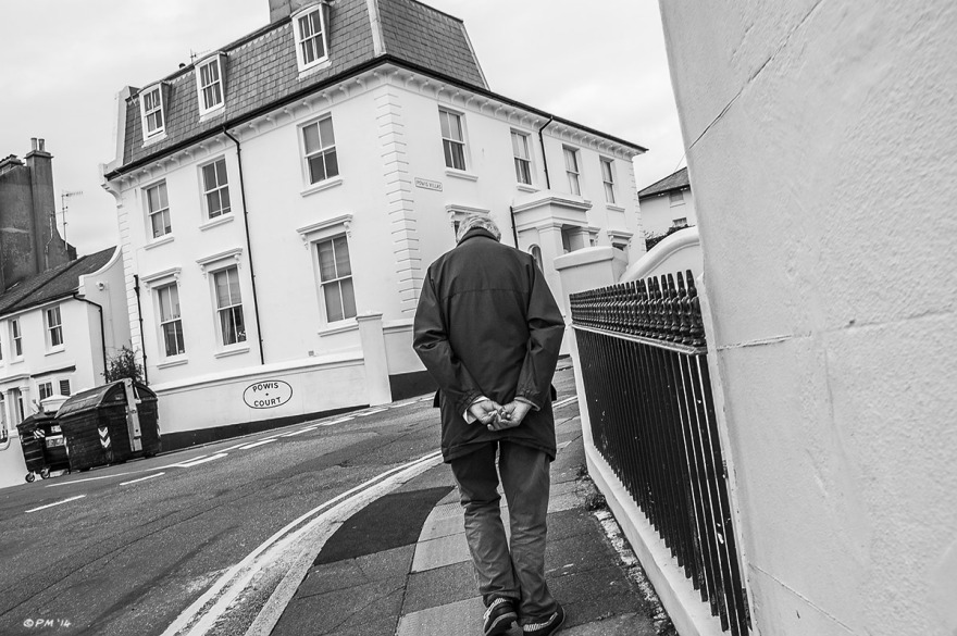 Old man walking away with gads behind his back and head down, up hill on Clifton Terrace with Powis Court in background, Brighton. Monochrome landscape. © P.Maton 2014 eyeteeth.net