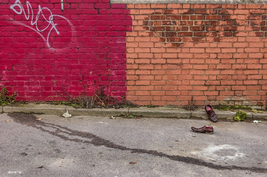 Discarded shoes with red lining by roadside next to red painted wall and stream of urine.  Abstract colour landscape. © P.Maton 2014 eyeteeth.net