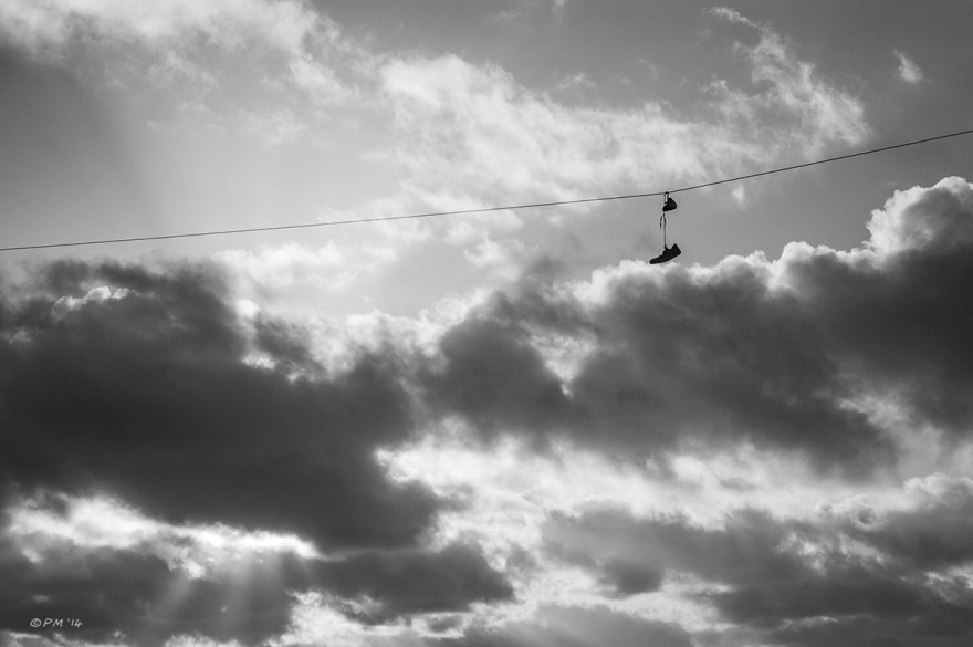 Shoes hanging by their laces on telegraph line with dramatic morning clouds in background. Monochrome landscape. © P.Maton 2014 eyeteeth.net