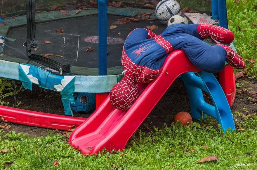 Soft Spiderman doll draped over children's slide in garden by trampoline with footballs. Colour landscape. © P.Maton 2014 eyeteeth.net