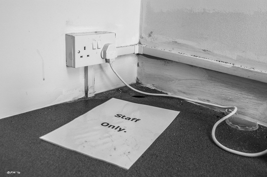 Staff Only notice lying on work top next to wall plug socket with cable extending out of shot. Abstract Monochrome Landscape. © P. Maton 2014 eyeteeth.net