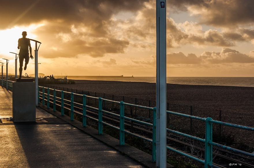 Steve Ovett Statue silhouetted  against morning sunrise on Madiera Drive with Brighton seafront and dramatic sky. colour landscape. © P. Maton 2014 eyeteeth.net