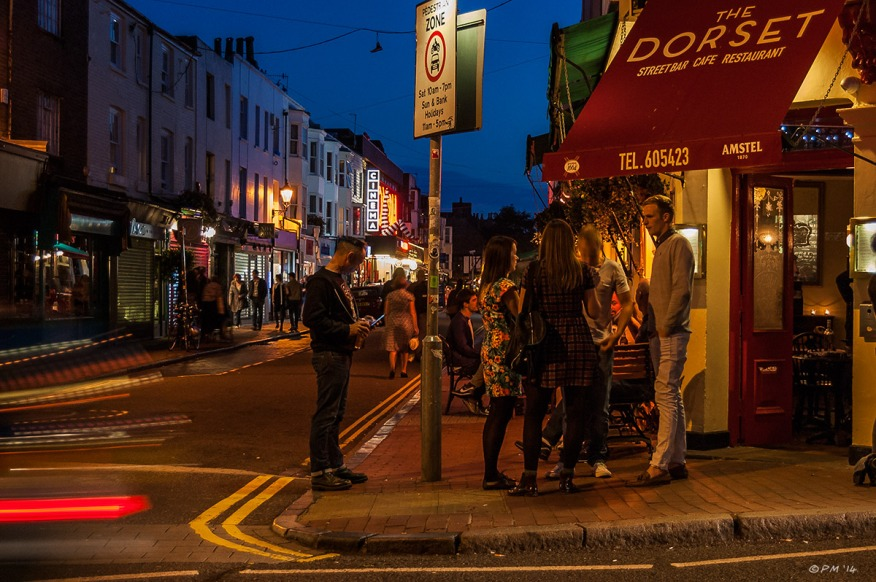 Colourful Night time view of people outside The Dorset Street Bar Gardner Street Brighton UK. Colour Landscape. © P.Maton 2014 eyeteeth.net