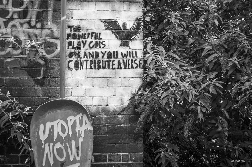 Political Graffiti on brick wall 'The powerful Play Goes on and you will contribute a verse' and 'Utopia Now' with Buddleia shrubs. Abstract Monochrome Landscape. © P.Maton 2014  eyeteeth.net