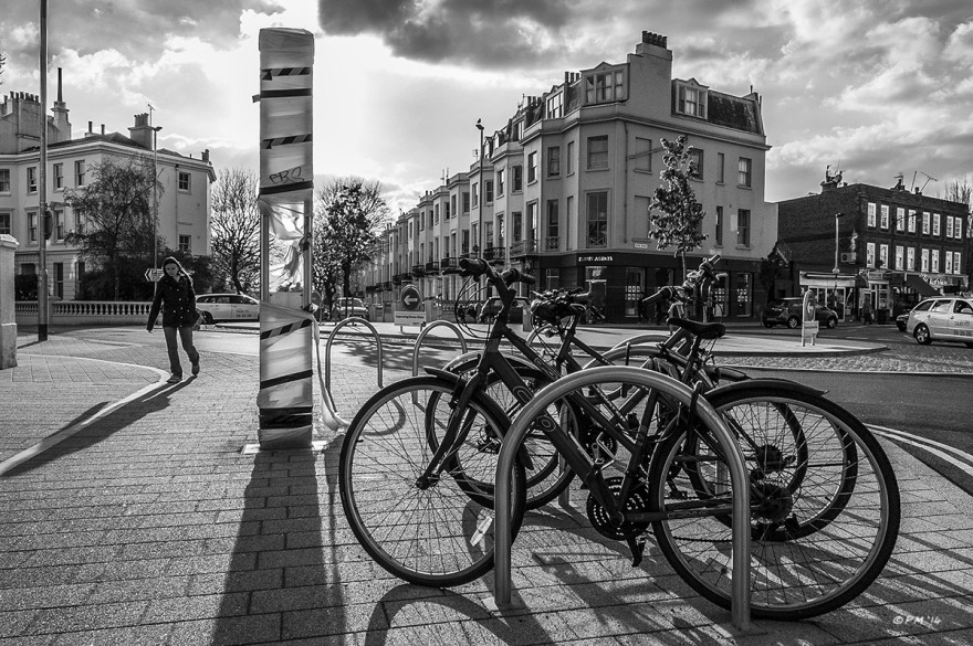 Seven Dials Roundabout new development with bicycle rack in foreground, dramatic clouds and long shadows towards viewer from sunlight. Street Photography Brighton UK. Monochrome Landscape. © P. Maton 2014 eyeteeth.net
