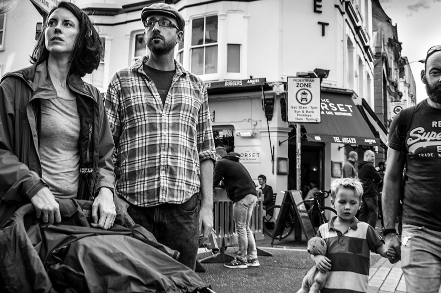 Man and woman with empty pram looking away out of shot, man and boy with bear, urban street scene. North Road Brighton UK. black and white urban street photography sussex. © P. Maton 2014 eyeteeth.net