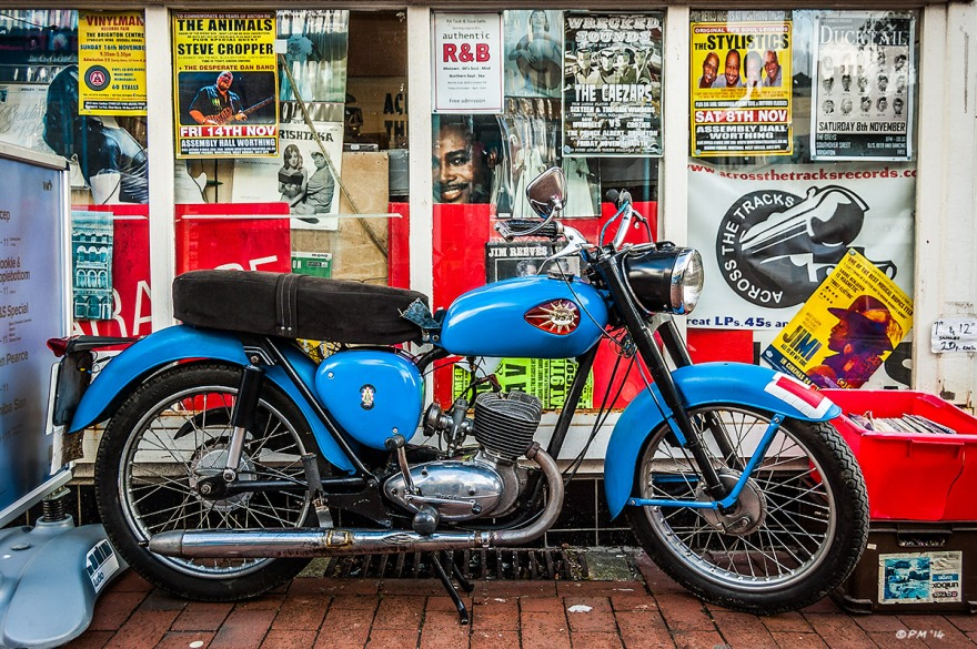 BSA Motorcycle outside Across The Tracks Record StoreSydney Street Brighton UK.. Colour landscape. © P.Maton 2014 eyeteeth.net