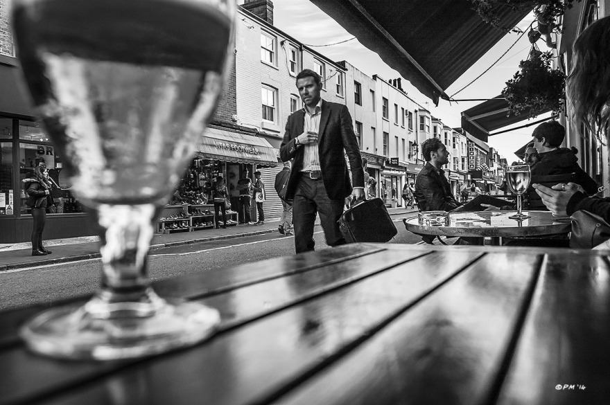 Man in sports jacket walking passed The Dorset Street Bar with table and glass of beer in foreground..Monochrome landscape. Gardner Street, Brighton, UK © P.Maton 2014 eyeteeth.net