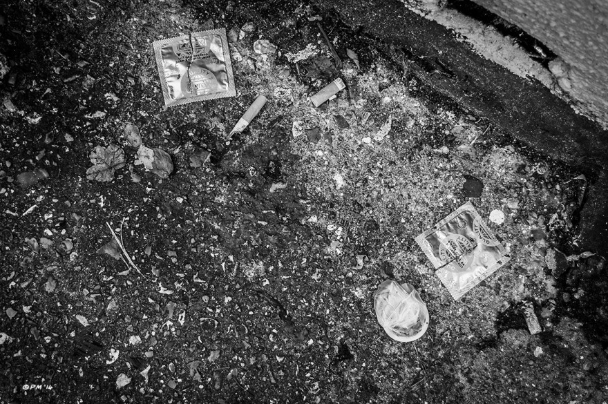 Torn condom wrappers and cigarette butts lying on tarmac in alley way, Brighton UK. Monochrome Landscape Abstract.  P. Maton 2014 eyeteeth.net