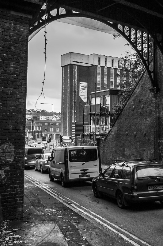 View under Victorian railway bridge toward Preston Circus showing Vantage Point building and  Brighton Housing Trust Shipping Container Housing for homeless people.  Monochrome portrait. © P. Maton 2014 eyeteeth.net