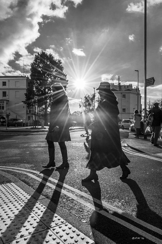 Two ladies crossing road silhouetted by sun flare on Seven Dials Roundabout, Brighton UK. Monochrome Portrait. © P. Maton 2014 eyeteeth.net