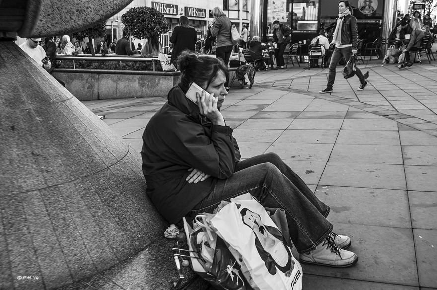 Lady on phone sitting next to shopping bags on Churchill Square Brighton UK. Monochrome Landscape. © P. Maton 2014 eyeteeth.net