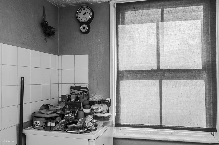 Interior of neglected kitchen with fridge piled with things and sunlight coming through blind. Monochrome Landscape.  P. Maton 2014 eyeteeth.net