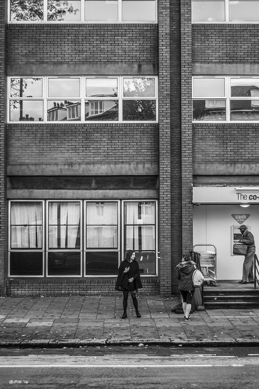 Two young ladies dwarfed by building break off from conversation outside the Co-Op store on Dyke Road Brighton UK. Monochrome portrait. © P. Maton 2014 eyeteeth.net