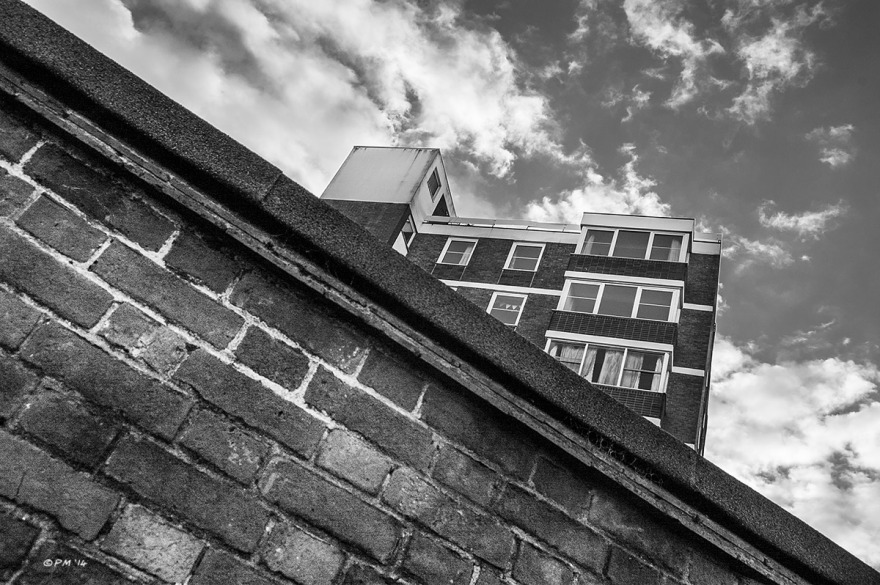 Block of flats seen over brick wall with scattered clouds in sky. Old Shoreham Road Brighton UK. Monochrome Landscape Abstract. © P. Maton 2014 eyeteeth.net