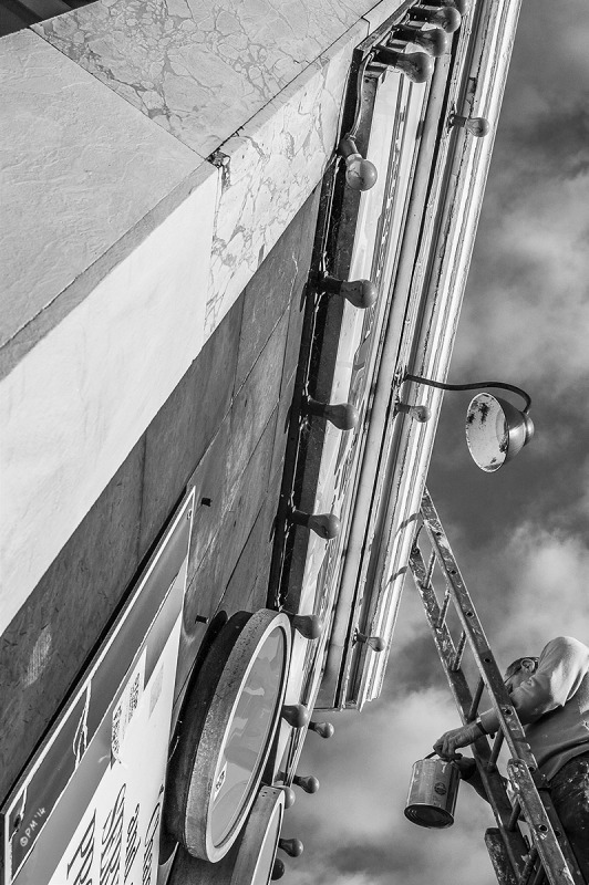 Man climbing ladder with pot of paint at front of launderette on Seven Dials Brighton UK. Monochrome portrait. © P. Maton 2014 eyeteeth.net