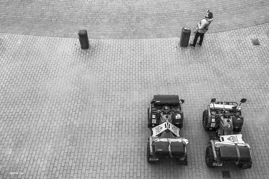 Two quad bikes parked on brighton seafront with woman brushing hair seen from above. Monochrome landscape. © P. Maton 2014 eyeteeth.net