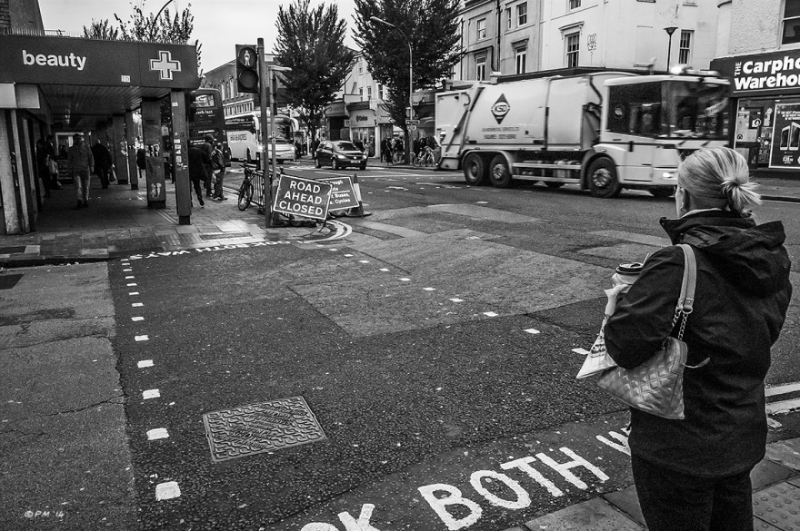 Woman stands at pedestrian crossing on an overcast day, London Road, Brighton UK. Monochrome Landscape. © P. Maton 2014 eyeteeth.net