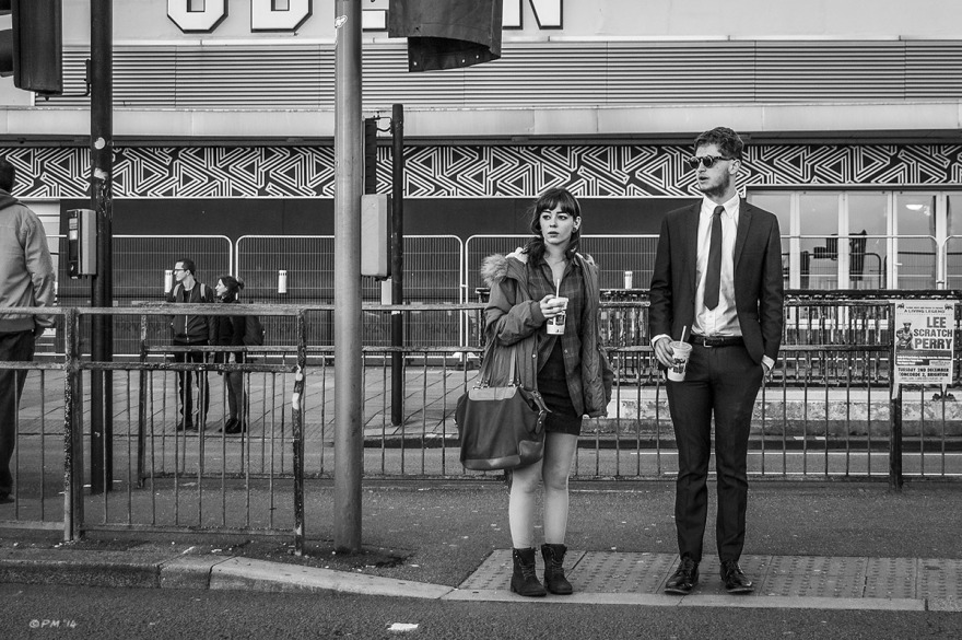 Young couple holding fast food drinks waiting at road crossing on Brighton seafront in front of Odeon Cinema, Brighton UK. Monochrome Landscape. © P. Maton 2014 eyeteeth.net
