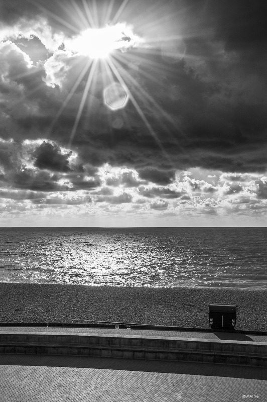 Sun flare breaking through clouds on Brighton Seafront. Monochrome portrait. © P. Maton 2014 eyeteeth.net