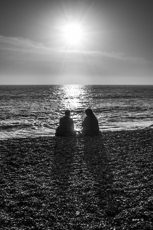 Two ladies talking while sat on Brighton Beach silhouetted by bright sunshine and casting long shadows across the shingle. Monochrome Portrait. © P. Maton 2014 eyeteeth.net