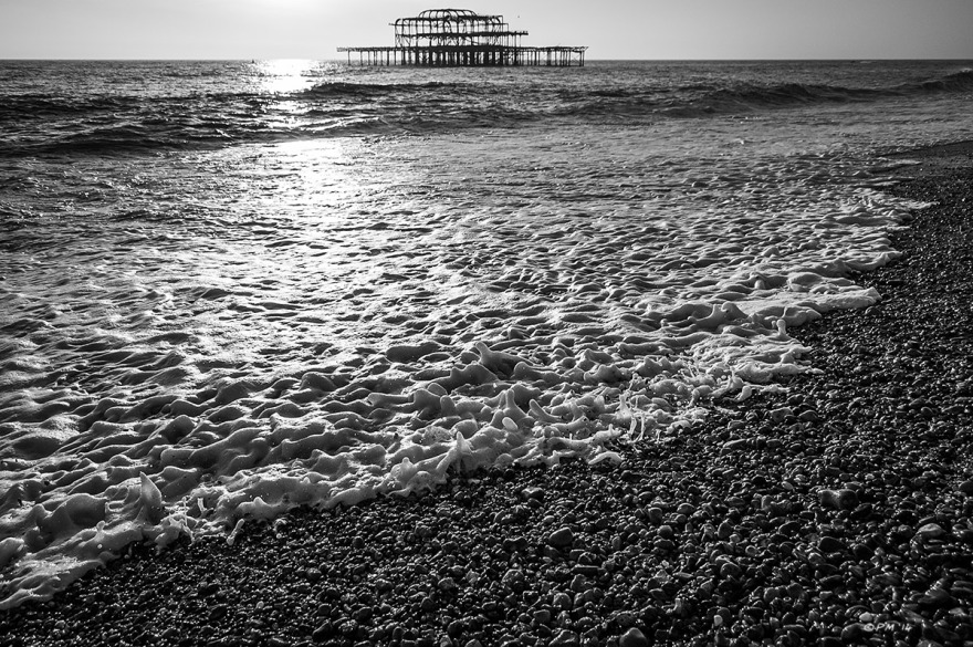 Ruins of West Pier and sunlight on sea with advancing water over shingle in foreground. Brighton UK. Monochrome Landscape. © P. Maton 2014 eyeteeth.net