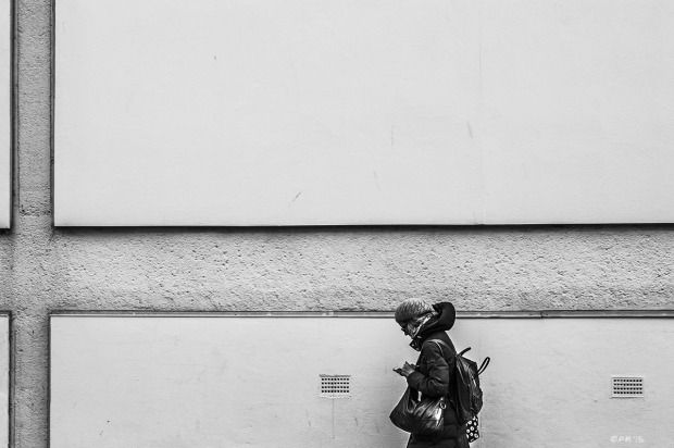 Woman looking at phone in from of wall . Abstract monochrome landscape. © P. Maton 2014 eyeteeth.net