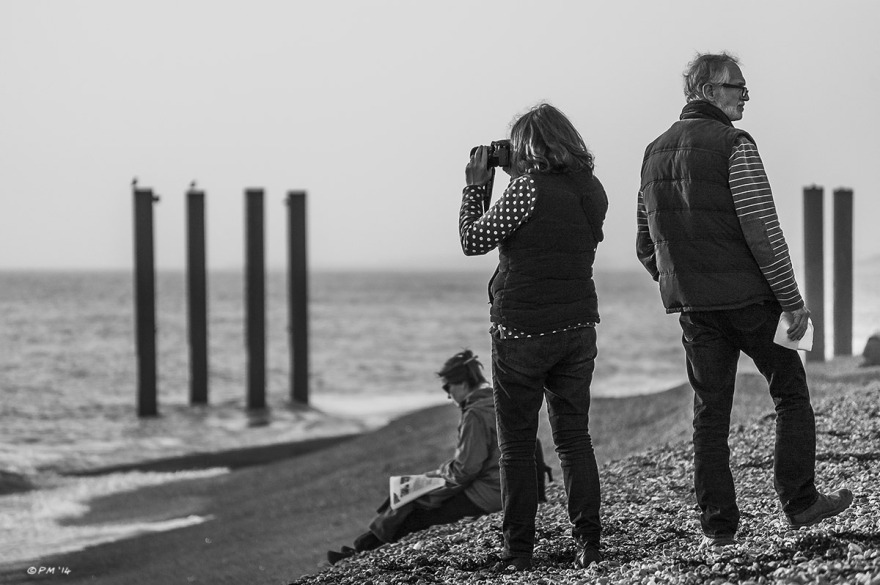 Woman standing, facing out to sea taking photo of West Pier while male partner looks in opposite direction and seated woman reads newspaper in background. Brighton Beach UK. Monochrome Landscape. © P. Maton 2014 eyeteeth.net
